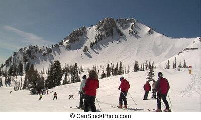 Many skiiers glide down mellow hill, blue sky