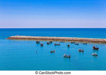 Many small boats lying near jetty in sea