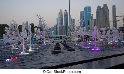 Many small splashing dancing fountains in summer Dubai park. Outdoor small fountains in order to refresh themselves in the summer. Slow motion