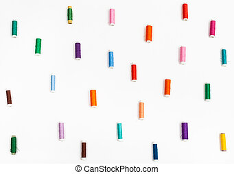 many spools of sewing thread on white