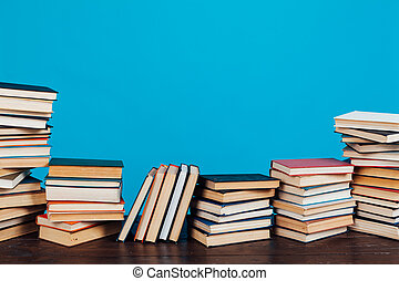 many stacks of educational books to teach in the library on a blue background