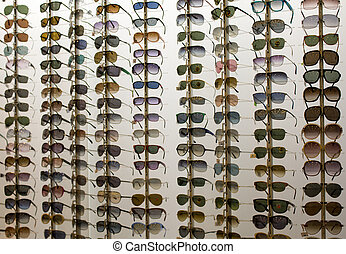 Many sunglasses on display in shop.
