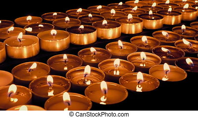 Many Tea Candles Burn In The Dark - Macro shot of small...