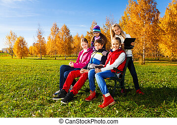 Many teens on the bench in park