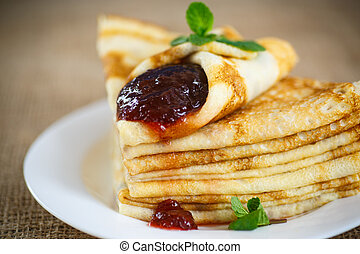 many thin pancakes with jam on the table