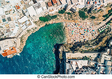Many tourists relax on beach in Poliano a Mare summer days, drone shot