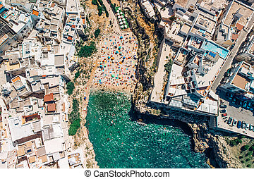 Many tourists relax on beach in Poliano a Mare summer days, top view