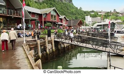 Many tourists walk on quay of coastal village at spring day