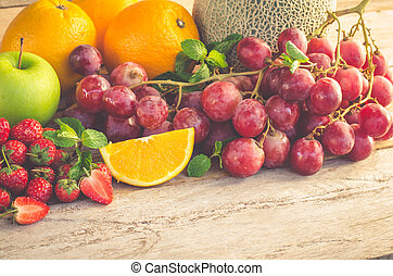 Many types of fruit placed on a wooden floor.