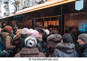Many unidentified people are waiting for city transport at the bus stop