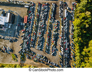 Many used car auction lot parked distributed in a parking.