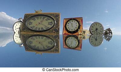 Many various clocks on the mirror beneath the cloudy sky,...