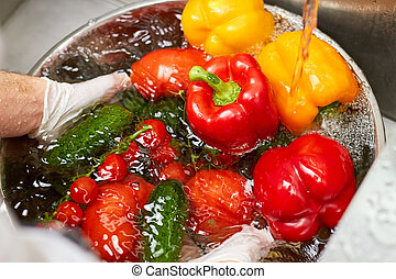 Many vegetables sinking in a bowl of water.