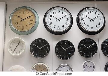 Many wall clock on the wall