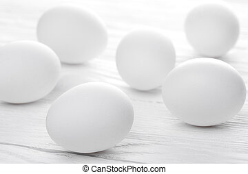 Many white eggs on the wooden teble