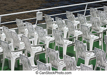 many white empty plastic chairs in rows