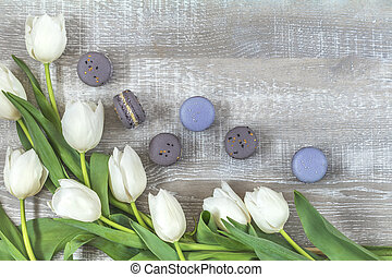 Many white tulips and gray macaroons on light wooden surface