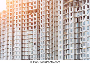 Many windows and balconies in a residential multi-storey building under construction.