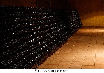 Many wine bottles in wine cellar of winery