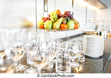 many wineglasses. Breakfast in restaurant of hotel. Plate with fruits and berries on a smorgasbord in the background. Bar