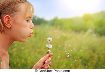 Many wishes - A girl blowing a dandelion flower against a...