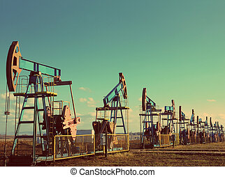 many working oil pumps in row - vintage retro style