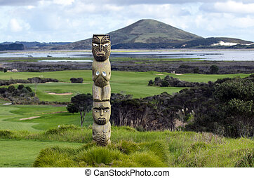 Maori carving against Rangiputa mountain in Karikari...