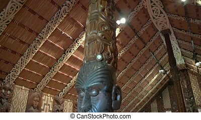 Maori carving in meeting house - Pan down shot in the Marae...