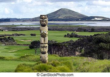 Maori carving against Rangiputa mountain in Karikari...
