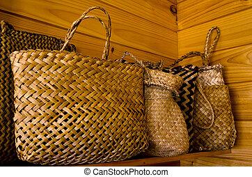 Maori flax bags - Traditional Maori flax bags on a shelf.