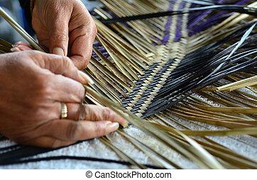Maori woven artwork - Hands of an old Maori woman weaving a...
