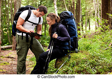 Map Camping - A couple of backpackers looking at a map in...