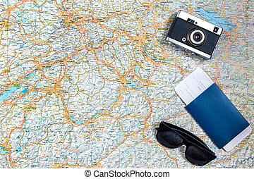 Map of roads with a vintage camera, passport, sunglasses. View from above. The concept of travel