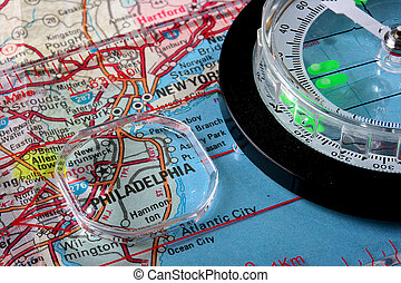 USA map with the city of Philadelphia and a compass with magnifying glass over Philadelphia.