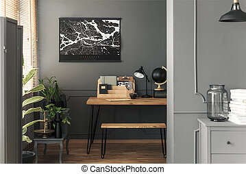 Map poster hanging on the wall in real photo of open space room interior with hairpin bench and desk with lamp, black globe wooden organizer and tea cup