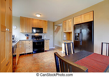 Maple cabinets in brown large kitchen