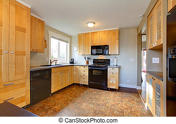 Maple cabinets in modern kitchen with brown walls