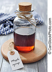 Maple syrup in glass bottle on a wooden background