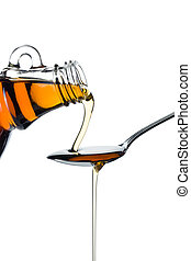maple syrup pourin on spoon on white background