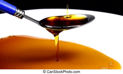 Maple syrup running down off a spoon