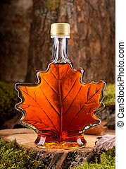 Maple Syrup - A bottle of delicious maple syrup in hardwood...