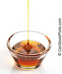 Maple syrup in a bowl on white background
