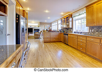 Maple wood cabinets in a large kitchen.