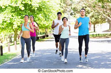 Marathon athletes running on street - Group of multiethnic...