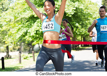 Marathon runner crossing finish line - Young marathon runner...