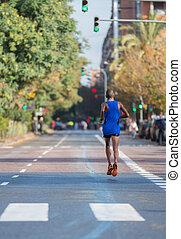 Marathon runner - Rear view of marathon runner running on...