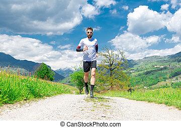 Marathon runner trains in a mountain dirt road