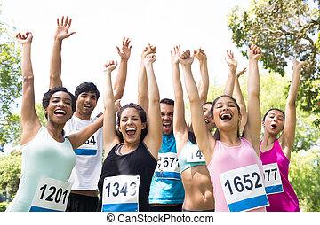 Marathon runners cheering in park - Group of marathon...