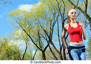 marathon - Young sporty woman is jogging outdoor.