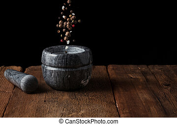 Marble mortar on old wooden table on black background with copy space. Pepper seeds fall into the mortar. freezer food